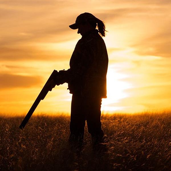 kvindelig jæger i solnedgang